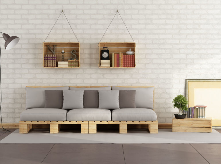 42906540 - living room with pallet sofa and wooden crate with books on brick wall - 3d rendering